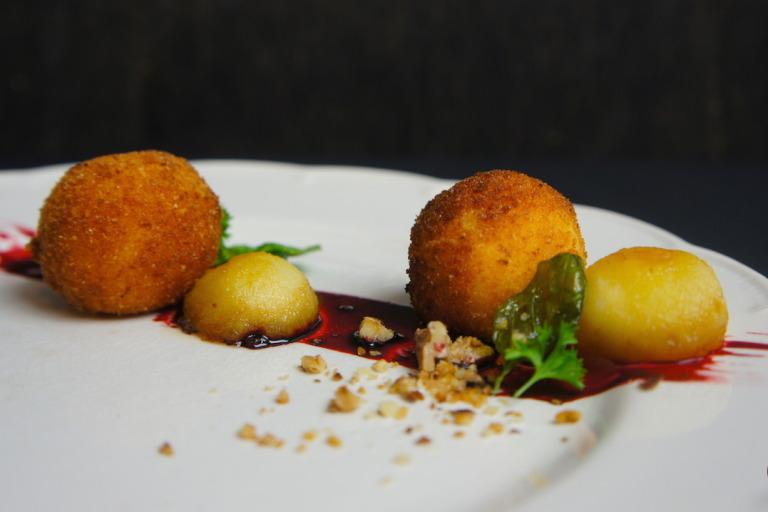 Geitenkaasbitterballen op port-bietenstroop met gekaramelliseerde appel, gefrituurde basilicum en walnootcrumble